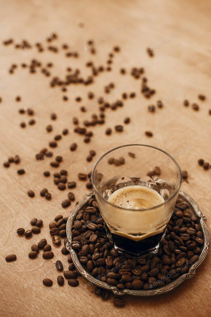 Heißer Espresso mit Schaumstoff in Glasbecher auf Vintage-Teller mit aromatischen gerösteten Kaffeebohnen