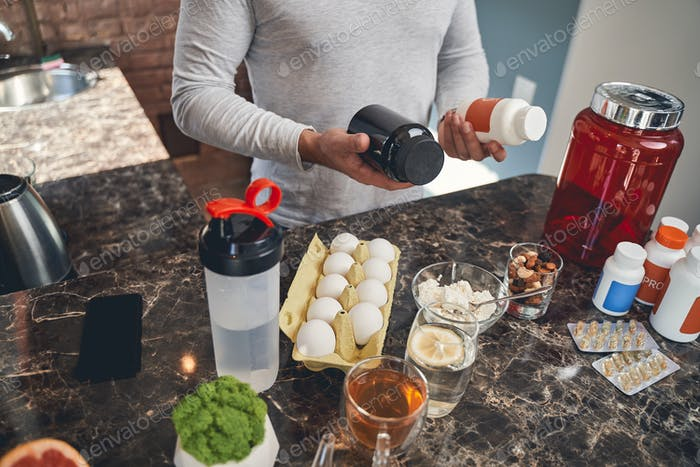 Sportsman with sports nutrition at the table