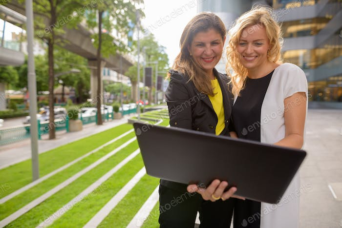 Portrait of two happy businesswoman using laptop computer together outdoors