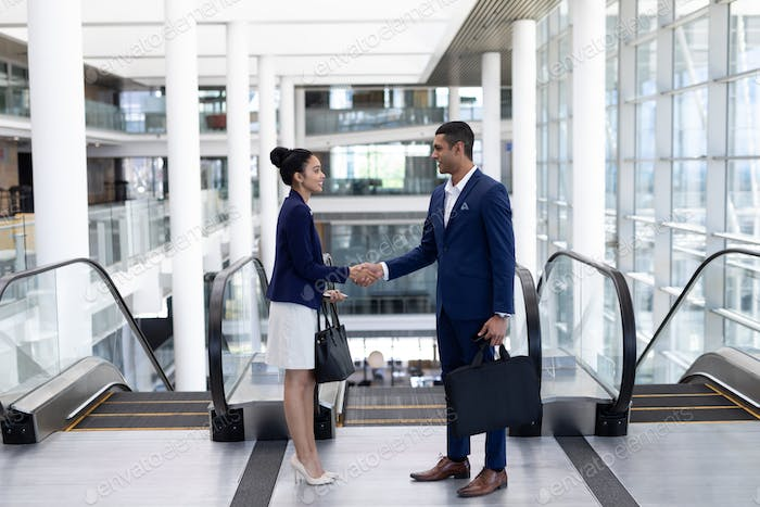 Side view of smiling young mixed-race business people shaking hand standing in modern office