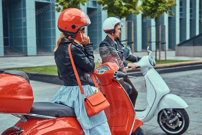 Atractiva pareja romántica sentada en scooters italianos retro contra un rascacielos.