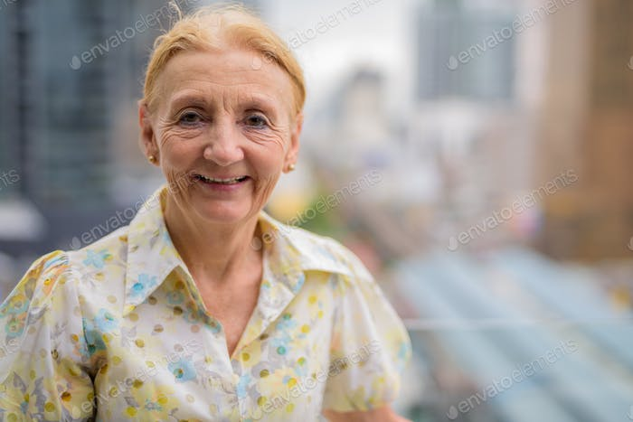 Happy beautiful senior woman smiling outdoors in city