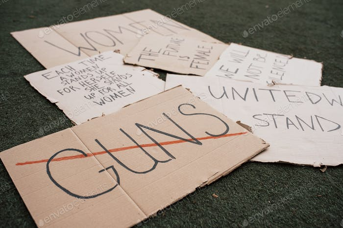 Say no to guns. Group of banners with different feminist quotes lying on the ground