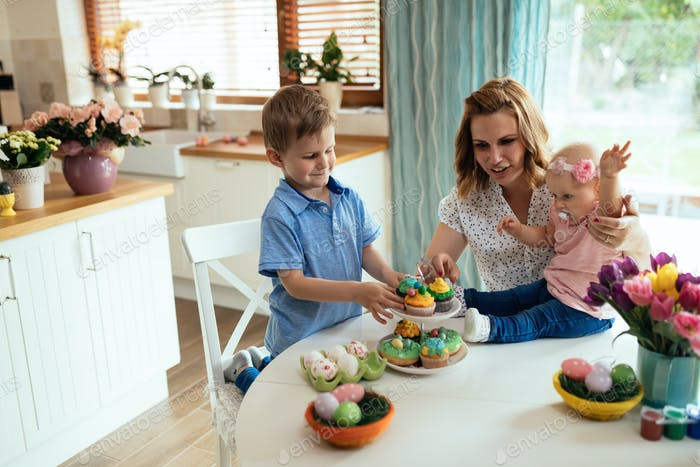 Happy children with mother eating cupcakes