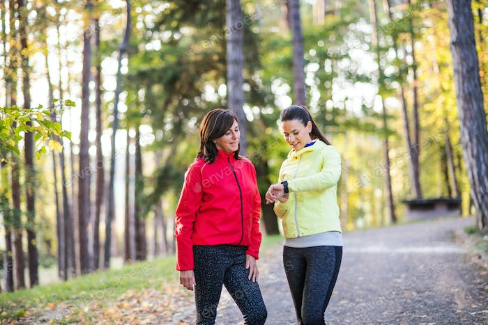 Female runners with smartwatch outdoors in forest in nature, checking the time.