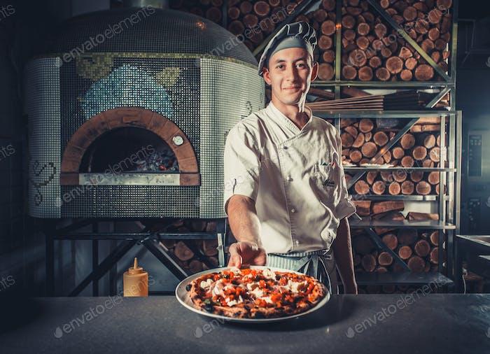 Man kocht hält frisch gekochte Pizza