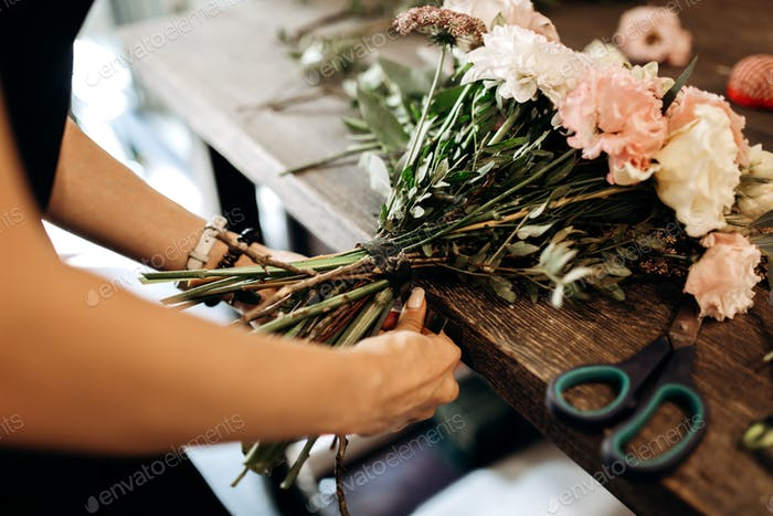 Florist ties a ribbon on the stems of flowers in flower shop