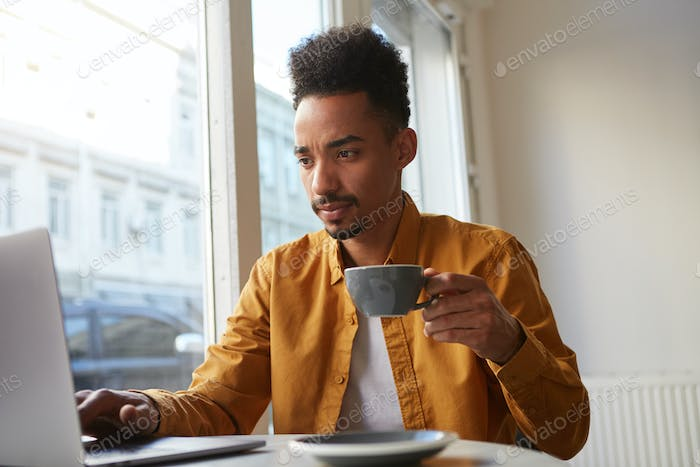 Young focused African American guy sitting at a table in a cafe and works
