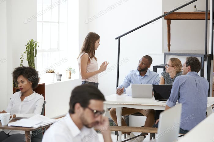 Colleagues in discussion around a desk in open plan office