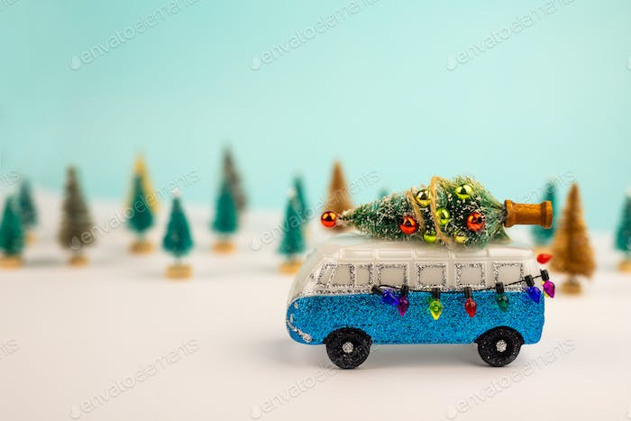 Miniature blue van with x-mas tree on is top.