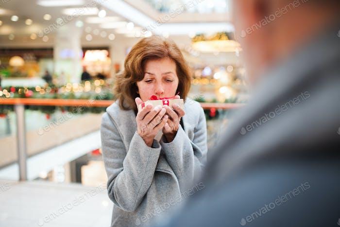 Senior couple with present doing Christmas shopping.