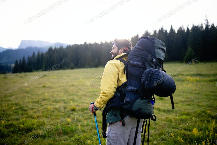 Adventure, travel, tourism, hike and people concept - man with beard and backpack hiking