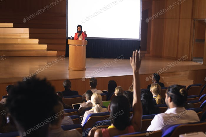 Rear view of mixed race woman sitting in audience raising hand for asking question