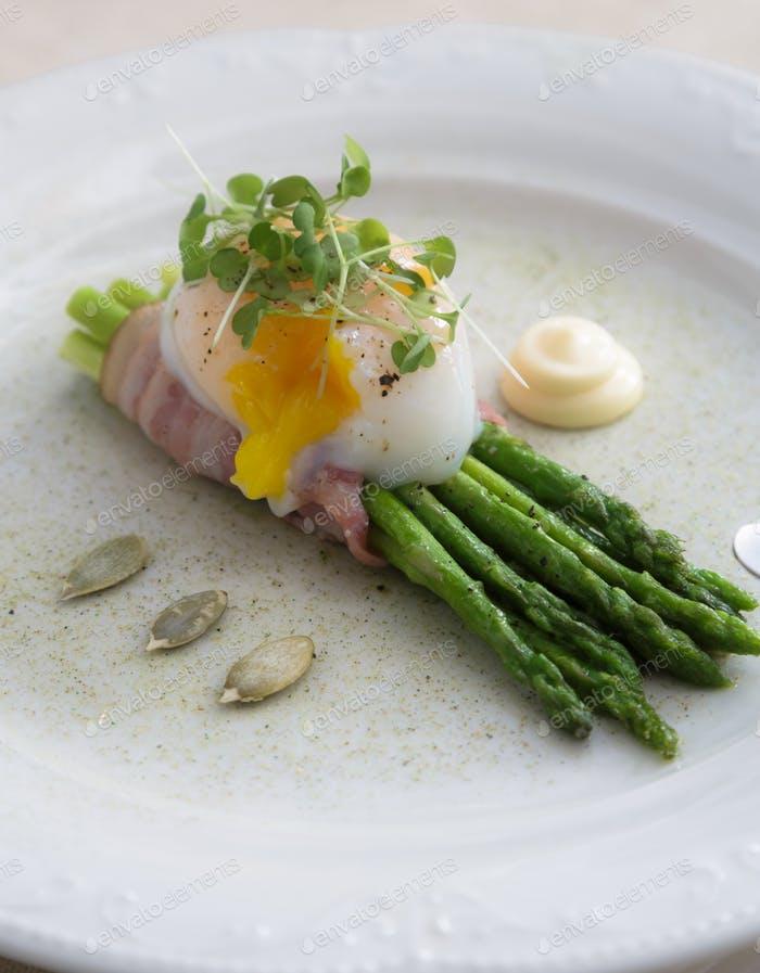 Poached egg over green asparagus on a plate