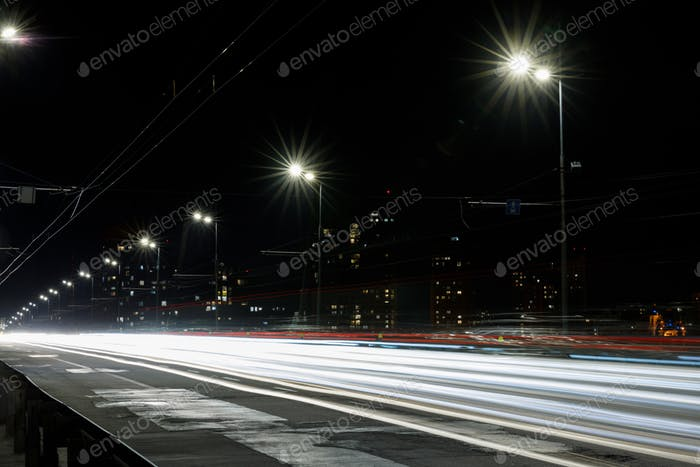 long exposure of lights on road at nighttime near buildings