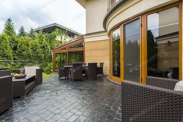 Elegant backyard terrace with rattan furniture