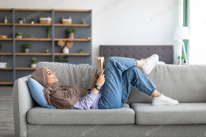 Muslim woman having rest at home, reading book