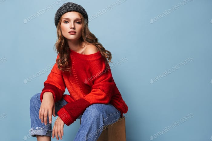 Young attractive woman with wavy hair in hat and red sweater thoughtfully looking in camera