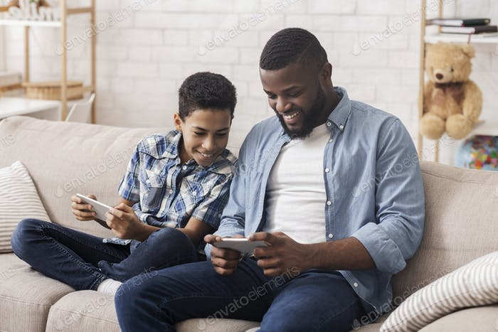 Cheerful Black Boy And His Dad Playing Video Games On Smartphones
