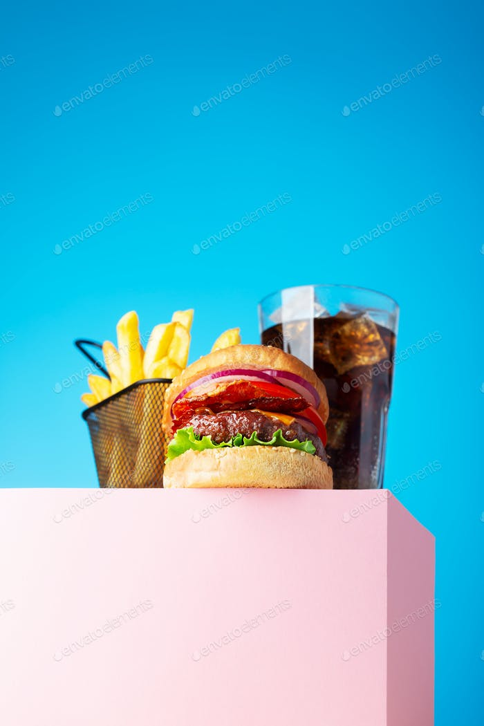 Fresh juicy beef hamburger, fried potatoes and drink, placed on the stand and blue background