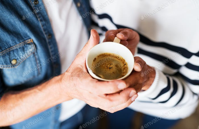 Unrecognizable senior couple holding a cup of coffee at home.