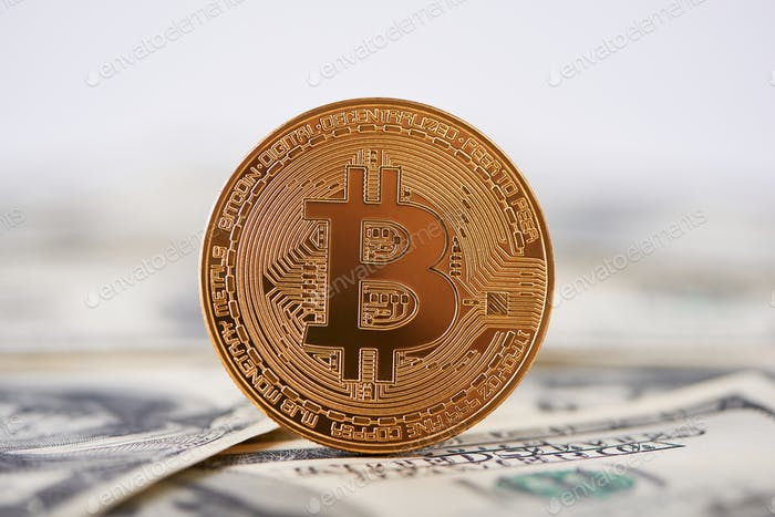Shiny golden bitcoin on edge standing on old hundred dollar banknotes
