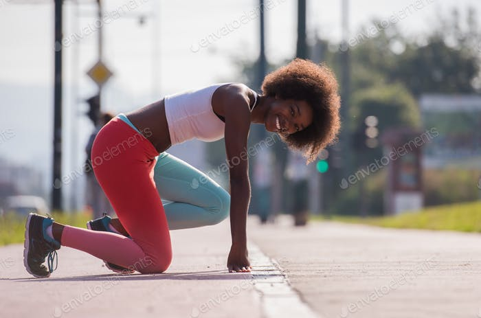 Portrait of sporty young african american woman stretching outdo