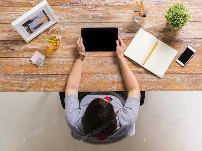 woman with tablet pc and notebook at office table