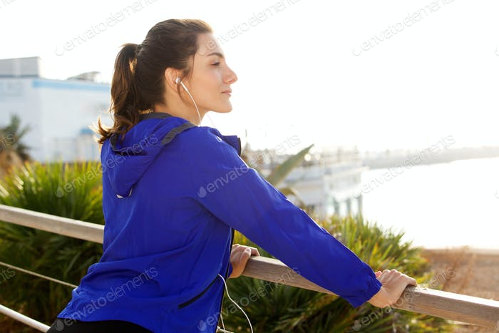 Side of serious athletic woman with headphones looking at view
