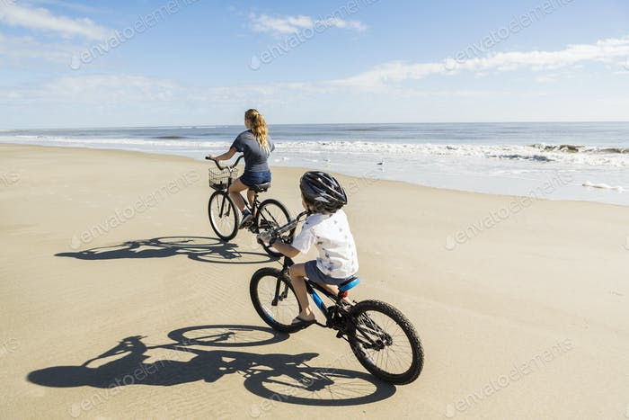 Children cycling on the sand by the water, a boy and girl.