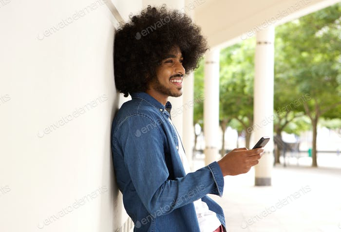 Smiling modern man standing outside with cell phone