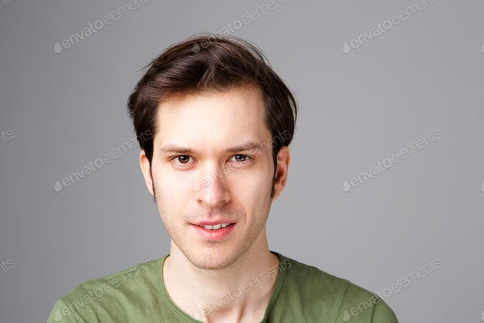 Close up confident young man standing by gray wall