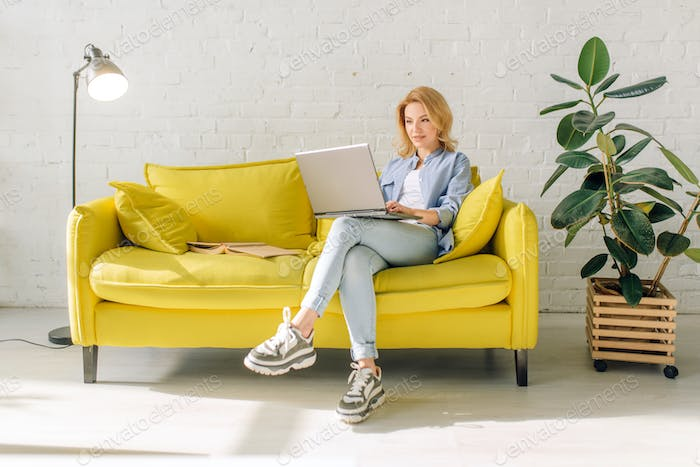 Young lady reading a book on cozy yellow couch