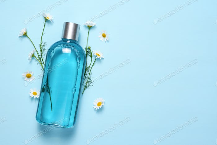 Cosmetic bottle and chamomile flowers on blue table top view with text space