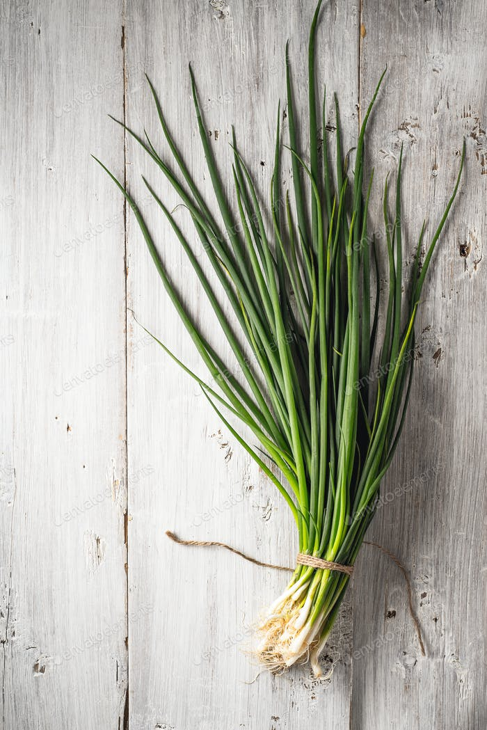 Green onion on the white wooden table top view