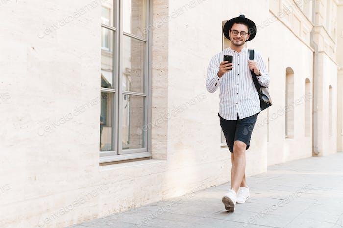 Foto von fröhlichen gutaussehenden Mann, der auf dem Handy tippt und lächelnd beim Gehen in der Stadtstraße
