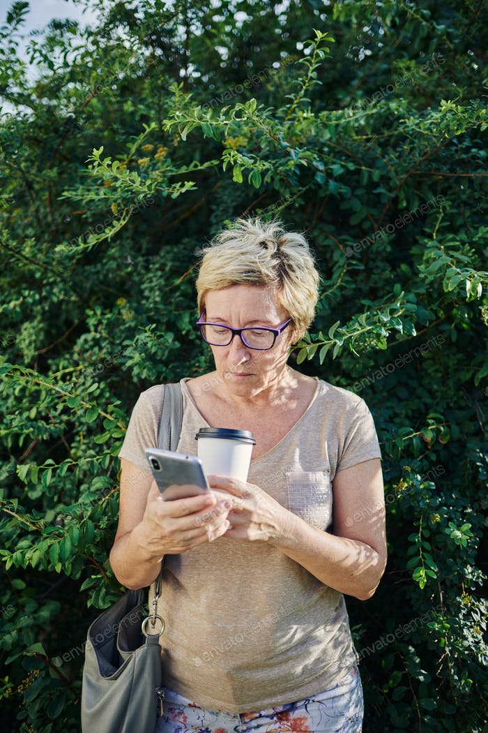 Senior woman using smartphone near bush