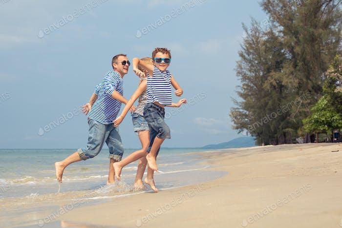 Vater und Kinder spielen am Strand am Tag Zeit.