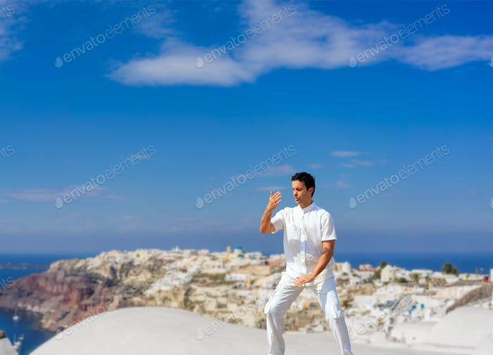 Handsome man practicing Tai Chi of the rooftops in Oia Santorini island