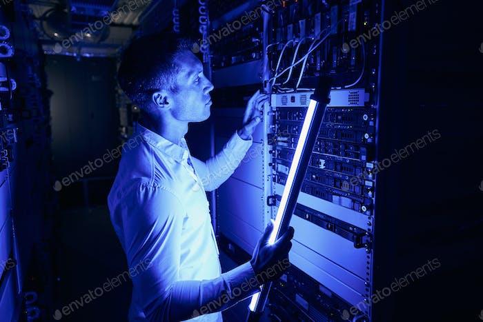 Focused IT technician lighting checking computer hardware