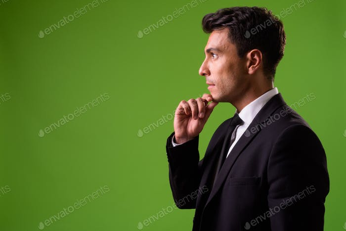 Young handsome Hispanic businessman against green background