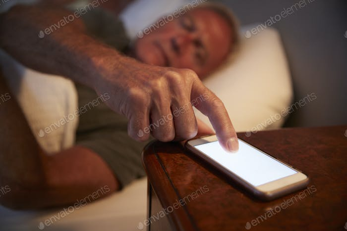 Sleepless Senior Man In Bed At Night Checking Mobile Phone