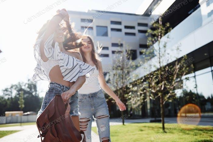 Zwei schöne Mädchen mit Rucksäcken gehen zusammen in der Stadt. Ziemlich niedliche Freunde teilen Geheimnisse