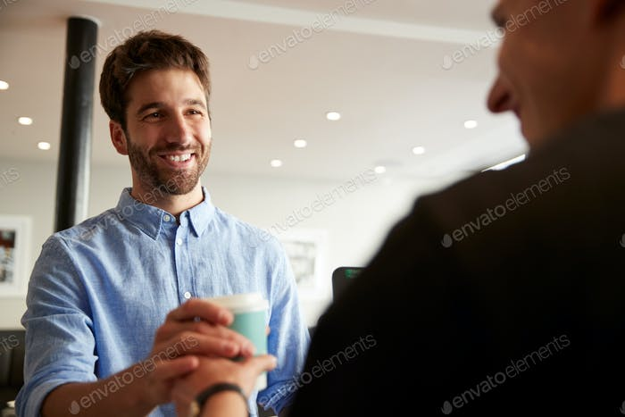 Male Barista Serving Customer With Takeaway Coffee