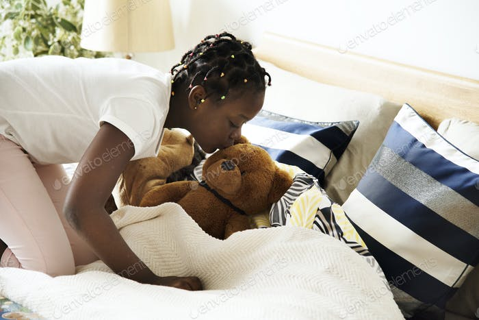 Young teen girl kissing a teddy bear