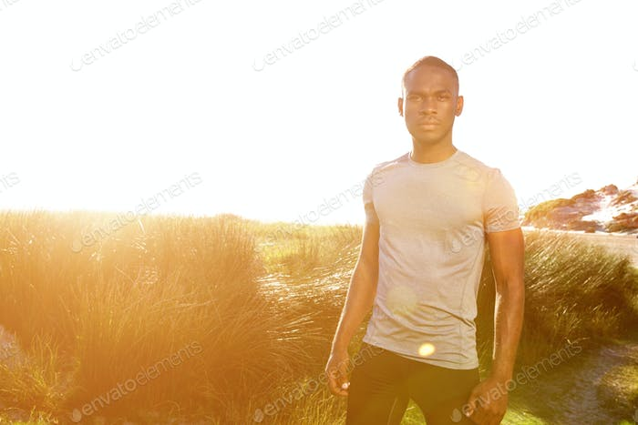 Young fitness man standing at the beach with bright sunlight
