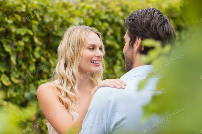 Young happy couple smiling at each other in the grape fields