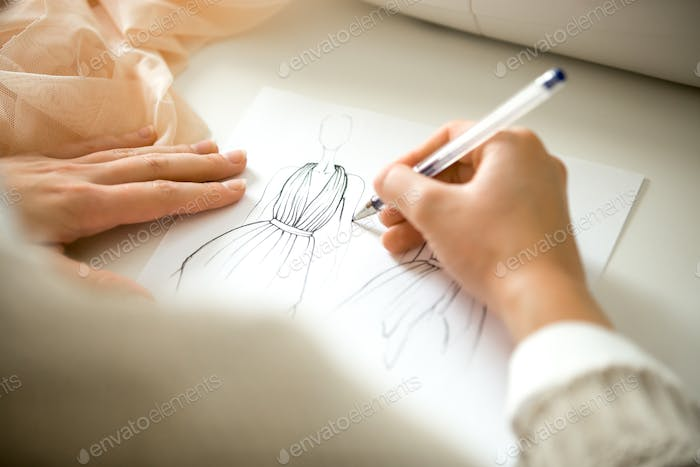 Hands drawing a clothing design sketch