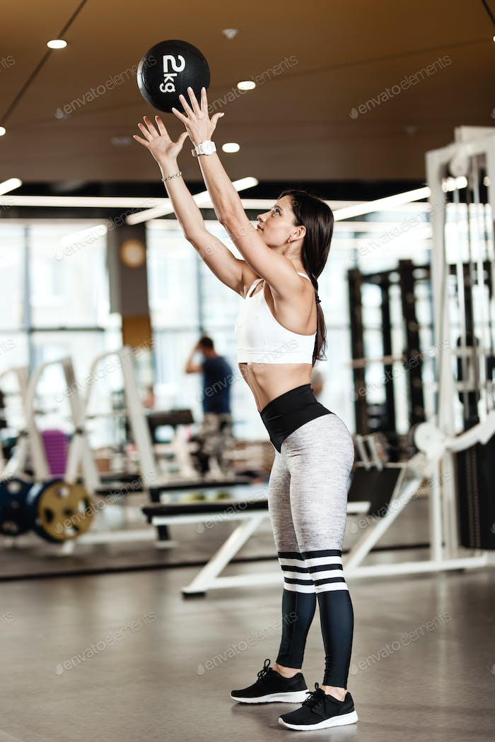 Athletic brunette girl dressed in a sportswear throws the fitness ball up in the modern gym