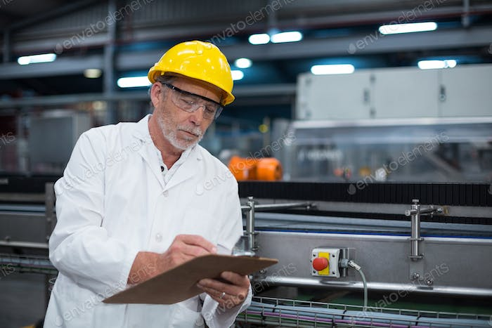 Factory engineer maintaining record on clipboard
